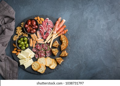 Still life, food and drink, holidays concept. Assortment of spanish tapas or italian antipasti with meat, ham, olives, cheese, nuts and bread on a black table. Top view flat lay copy space background
