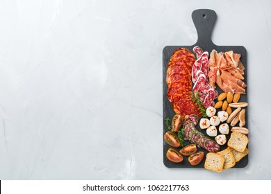 Still life, food and drink, holidays concept. Assortment of spanish tapas or italian antipasti with meat, ham, olives, cheese, nuts and bread on a table. Top view flat lay copy space background