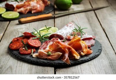 Still life, food and drink, holidays concept. Assortment of spanish tapas or italian antipasti  (jamon, prosciutto, chorizo, salami) on a grunge black board (rustic style). Selective focus