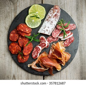 Still life, food and drink, holidays concept. Assortment of spanish tapas or italian antipasti  (jamon, prosciutto, chorizo, salami) on a grunge black board (rustic style). Selective focus, top view