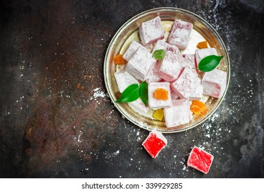 Still life, food and drink, seasonal and holidays (ramadan, seker bayram) concept. Rose turkish delight on a metal grunge table. Selective focus, copy space background, top view