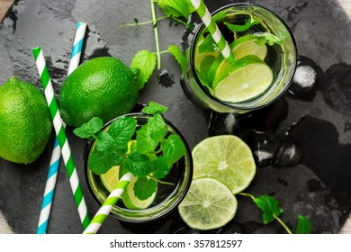 Still life, food and drink, seasonal and holidays concept. Mojito cocktail and ingredients on a grunge black table. Selective focus, top view