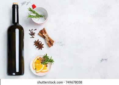 Still life, food and drink, seasonal and holidays concept. Christmas new year hot warm beverage, mulled wine ingredients, bottle, spices, orange, rosemary. Top view flat lay copy space background