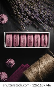 Still life, food photography. Pink macaroons on a dark wood background. Lavender and flagella.