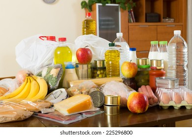 Still life with foodstuffs of supermarket on table in home interior