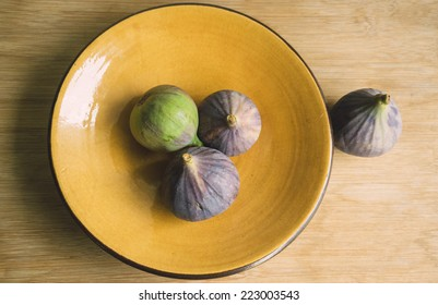 Still life of four figs on yellow plate