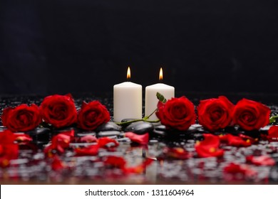 Still life with four red rose ,petals with candle and therapy stones