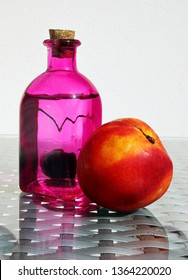 Still life with fresh compote in vintage glass botlle, nectarine and ripe cherry against a high key background with space for your text. Selective and soft focus.