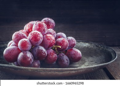Still life of fresh, dark red grapes with water splashes on dark background