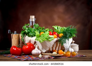 Still life of fresh tomatoes, garlic and parsley on wooden boards.