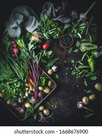 Still life of fresh vegetables, herbs and berries. Top view, flatlay on dark wooden background. Healthy eating concept.