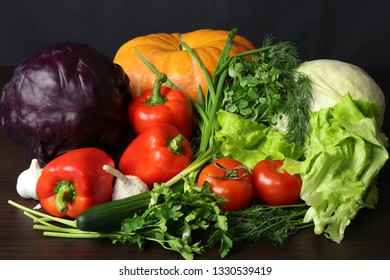 Still life of fresh vegetables. Pumpkin, white cabbage, red cabbage, two tomatoes, large and juicy red sweet peppers, greens of Basil, dill, parsley and green onions, as well as green fresh cucumber..