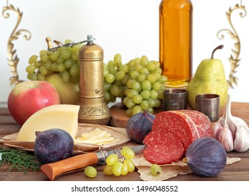 Still life with fruit, cheese and salami. In the foreground are figs and grapes. Close-up.