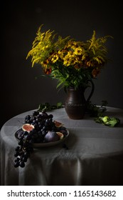 Still life with fruits and flowers on the table. Dark tone.