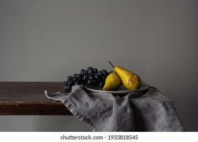 Still life with fruits. Grapes and pears on a rustic table indoors with a moody window light - Shutterstock ID 1933818545