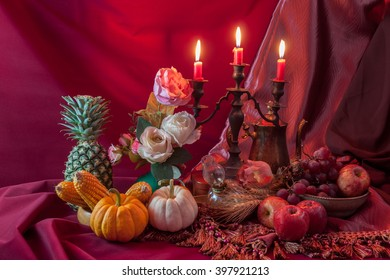 Still life of fruits and vegetable on the table and candle stand