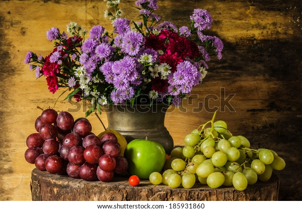 Still Life Fruits were placed on the timber with a beautiful vase of flowers.