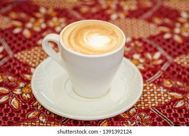 Still life of a full coffee cup on the tablecloth ready for someone to enjoy.