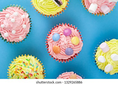 Still life of fun bright colors children Easter celebration cupcakes with chocolate candy and marshmallows, interior vivid table background space. Kids dessert cooking food, sweet eating flavour.