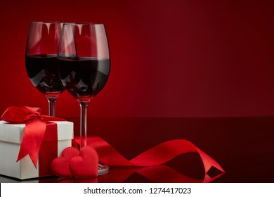 Still life with gift box, red satin hearts and two glasses with wine on a red background. Valentine's Day card with copy space. Design element for romantic greeting card, wedding invitation,