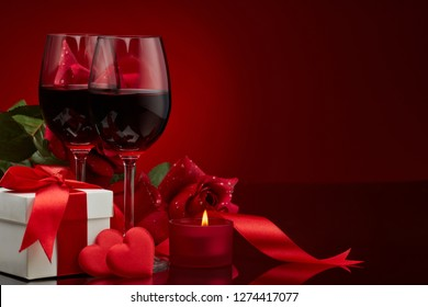 Still life with gift box, roses, red satin hearts and two glasses with wine on a red background. Valentine's Day card with copy space. Design element for romantic greeting card, wedding invitation,