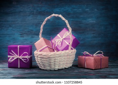 Still life with gift boxes in basket over blue wooden background.