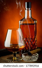 still life with glass and bottle of brandy and smoking cigar