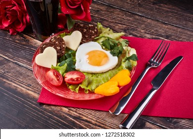 Still life with glass of juice, roses and dish with fried egg, bread, cheese and vegetables in the shape of a heart on a wooden background. Top view. Breakfast on Valentine's Day