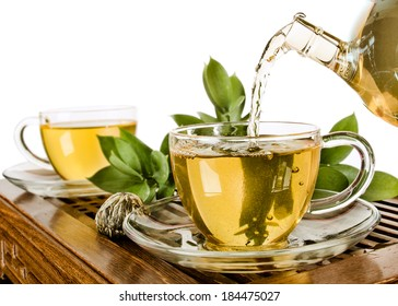 still life of the glass teapot flow green tea in cup on white background, isolated,  tea ceremony