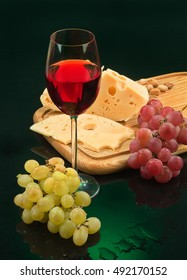 Still life with a glass of wine, grape and cheese
