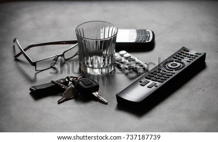 Still life with glasses, car keys, tablets, TV remote control