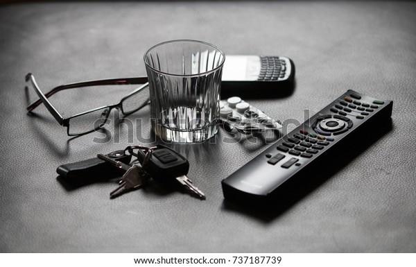 Still life with glasses, car keys, tablets, TV remote control