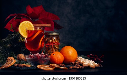 Still life with glasses of mulled wine or fruit tea, Red Poinsettia flowers, fir branch and spices on a dark background with copy space. New year and Christmas table setting. Greeting card.