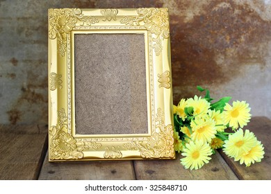 Still Life, Golden picture frame and yellow flower on wooden background