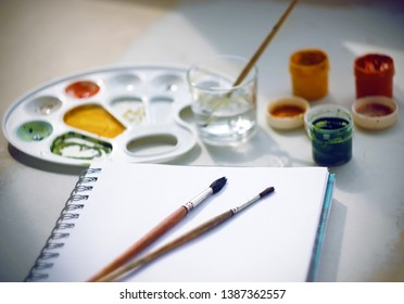 Still life with gouache paints yellow, red and green, a plastic palette, a notebook on a spring for drawing, brushes and a glass of water for washing brushes and diluting gouache.