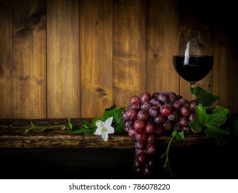 Still life of grapes with grape vine and a glass of grape juice on a wooden slab and wooden back drop in a dim light room