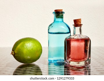 Still life with green lime and cold fresh lemonade in two small vintage glass botlles against a high key background with space for your text. Selective and soft focus.