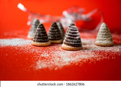 Still life with group of christmas beehive cake on snowy red background with blurred silver ribbon, greeting card.
