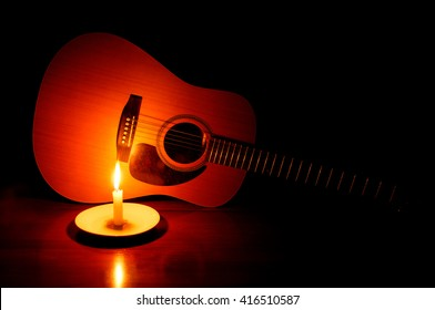 Still life of a guitar in the glow of a lit candle.