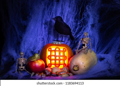 Still life of Halloween with toy black bird, toy skeletons, lit carved pumpkin with Celtic symbol for Samhain/Celtic New Year/Holloween, fruit, nuts and veg against a dark fake spider web background.