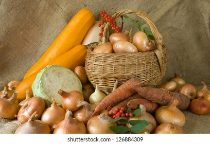 still life from harvested onion  in basket and vegetables on sacking