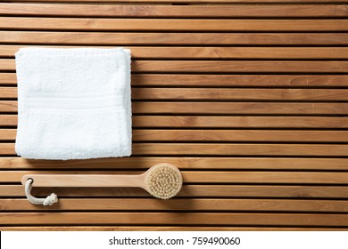Still life for healthy dry brushing, hygiene, bath, exfoliation or traditional body care concept with body brush and pure white towel over beautiful wooden board, copy space wallpaper, top view