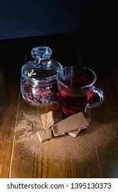 still life hibiscus tea in a mug and dry tea in a jar on a dark background