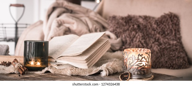 still life home atmosphere in the interior with a book and candles, on the background of cozy bedspreads, home decor elements, the concept of comfort and coziness