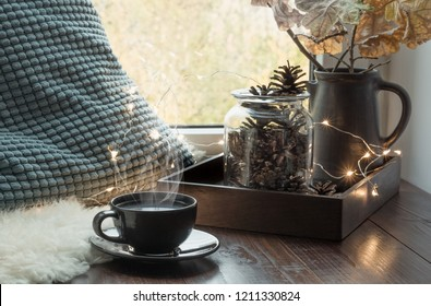 Still life in home interior. Cozy winter or autumn cup of coffee at home warm fluffy furskin , garland, swedish hygge concept.