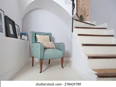 Still life home interior of an elegant armchair in a stylish home with cushions under an arch and next to stone walls and stairs, indoors. Reading room with picture frames, aspirational lifestyle.