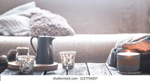 still life from home interior on a wooden background with a candle and a small kettle with a beautiful glass, home comfort concept