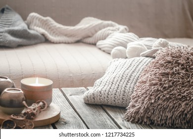 still life from home interior on a wooden background with a candle and pillows, home comfort concept