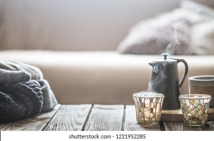still life from home interior on a wooden background with a small kettle and a beautiful glass, home comfort concept