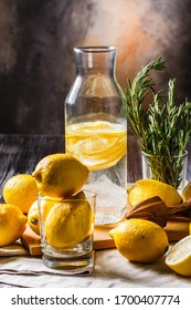 still life with homemade lemonade. a bottle of lemonade with lemon slices on a table littered with lemons. rustik